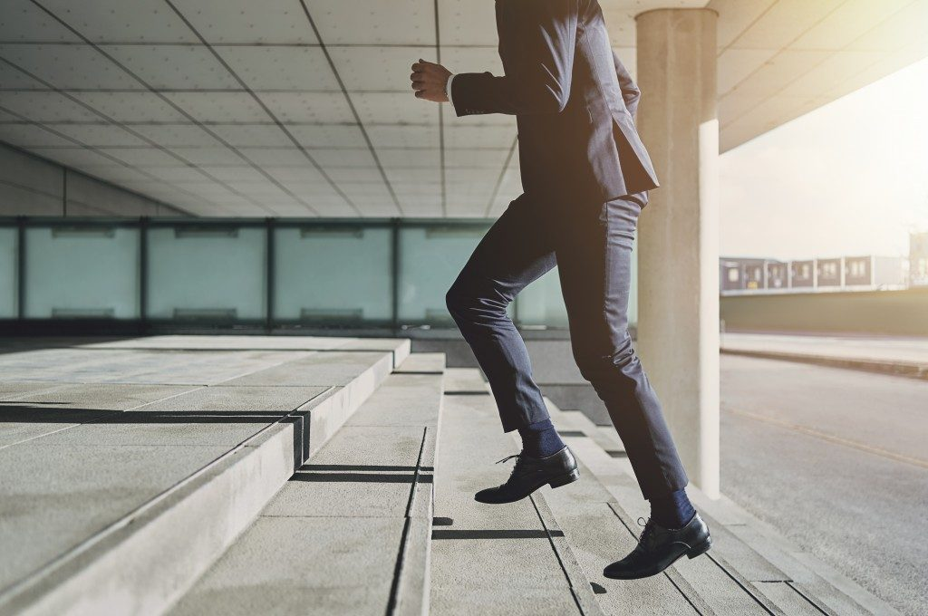 Man going up a stair wearing corporate attire